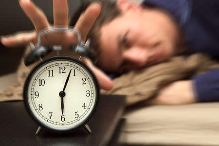despertarse: Despertador con modelo masculino en la cama en segundo plano. Profundidad de campo, desenfoque de movimiento para mostrar la realizaci�n cr�tica