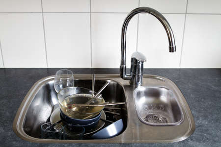 Dirty dishes in wash basin. High contrast, vivid, shiny photo