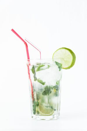 Mojito cocktail in a transparent glass with ice. Recipe for exotic drinks with mint, lime and white rum. Glass with a cocktail on a white background in the rays of the sun
