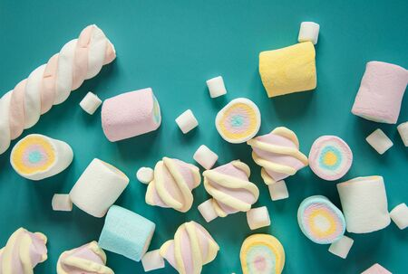 Natural marshmallows sweets on a blue background. Airy multicolored marshmallows sprinkled on the table.
