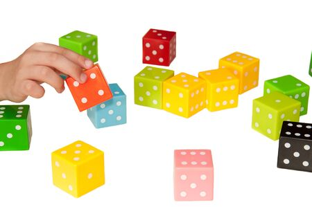 Cubes multi-colored game childrens puzzle, the development of logic and team thinking. Childrens hands hold colored cubes on a white background. Stok Fotoğraf