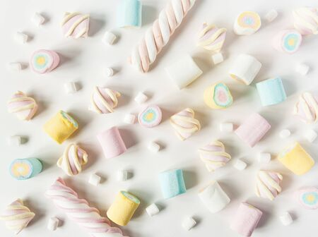 Natural marshmallows sweets on a white background. Airy multicolored marshmallows sprinkled on the table.