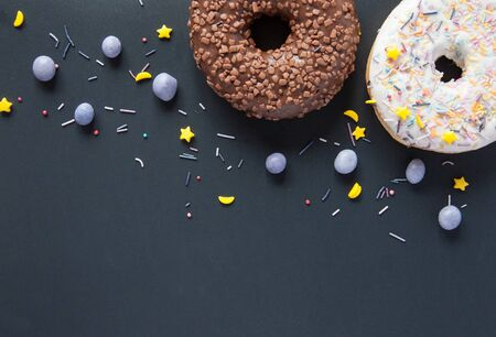 Sweet donuts on a black background with chocolate and berries.