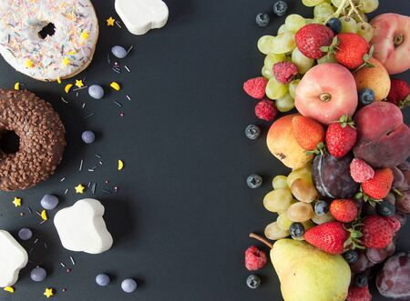 A lot of natural and healthy vitamin fruits, berries vs sweet and junk food on a black background. Vegan eco safe food. The right foods for weight loss and the wrong foods for weight gain. The choice Stok Fotoğraf
