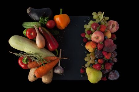 A lot of natural and healthy vitamin fruits, berries and vegetables natural products on a black background. Vegan eco safe food. Proper weight loss food.
