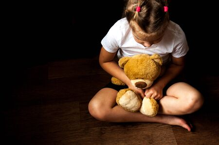 A sad little girl sits with a toy in her hands. Problems with raising children. Childrens shelters. Lonely and abandoned children. Banque d'images - 131702174
