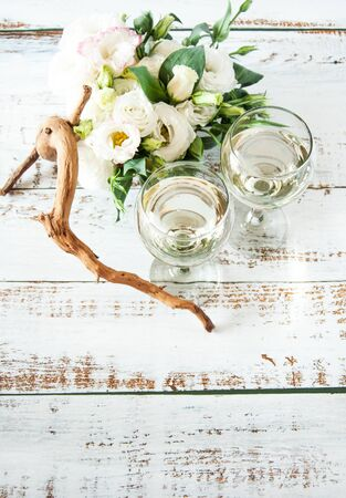 Glasses with wine on a white rustic wooden background with a bouquet of flowers. Wedding table greeting card. Wedding invitation light background.