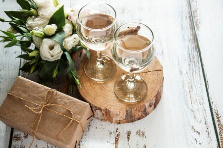 Glasses with wine on a white rustic wooden background with a bouquet of flowers and craft gift. Wedding table greeting card. Wedding invitation light background. Stok Fotoğraf