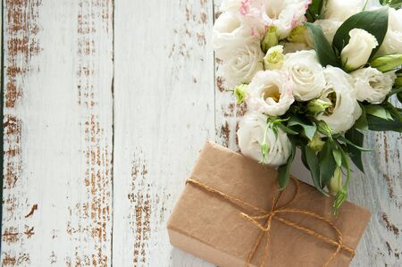 white rustic wooden background with a bouquet of flowers and craft gift. Wedding table greeting card. Wedding invitation light background Stok Fotoğraf
