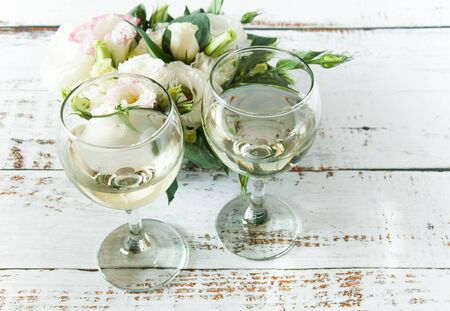 Glasses with wine on a white rustic wooden background with a bouquet of flowers. Wedding table greeting card. Wedding invitation light background