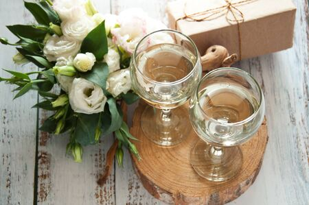 Glasses with wine on a white rustic wooden background with a bouquet of flowers and craft gift. Wedding table greeting card. Wedding invitation light background Stok Fotoğraf
