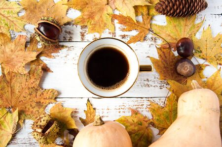 Autumn mood. Yellow, orange maple leaves on a wooden background, pumpkins and a cup of coffee. A lot of dry leaves and chestnuts, a hot drink, comfort. Natural materials