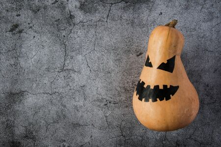 Autumn mood. Pumpkin with a scary face and yellow maple leaves to Halloween. Jack Lantern Pumpkin. Dark gloomy background Stok Fotoğraf - 131703029