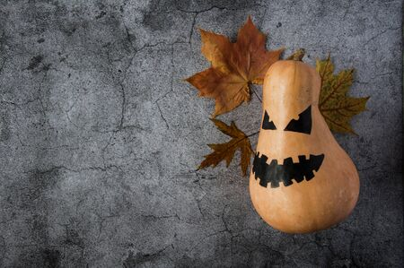 Autumn mood. Pumpkin with a scary face and yellow maple leaves to Halloween. Jack Lantern Pumpkin. Dark gloomy background