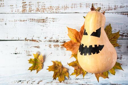 Autumn mood. Pumpkin with a scary face and yellow maple leaves to Halloween. Jack Lantern Pumpkin. Light wooden background
