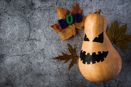 Autumn mood. Pumpkin with a scary face and yellow maple leaves to Halloween. Jack Lantern Pumpkin. Dark gloomy background Stok Fotoğraf - 131702618