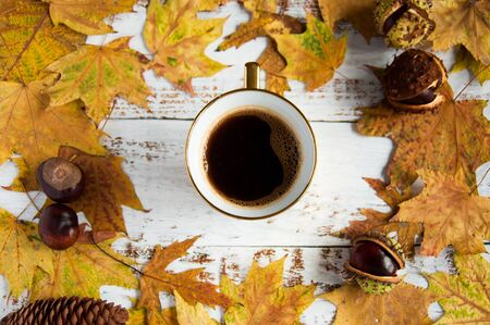 Autumn mood. Yellow, oraAutumn mood. Yellow, orange maple leaves on a wooden background and a cup of coffee. A lot of dry leaves and chestnuts, a hot drink, comfort. Natural materials