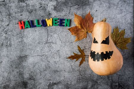 Autumn mood. Pumpkin with a scary face and yellow maple leaves to Halloween. Jack Lantern Pumpkin. Dark gloomy background Stok Fotoğraf - 131702591