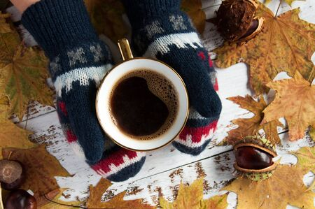 Autumn mood. Yellow, orange maple leaves on a wooden background and a cup of coffee in the hands. A lot of dry leaves and chestnuts, a hot drink, warm mittens, comfort. Natural materials