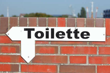 toilet sign: Toilet Sign with Arrow on a Brick Wall Stock Photo