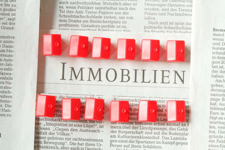 immobilien: Newspaper, Text Property (Immobilien in german), red small toys Houses