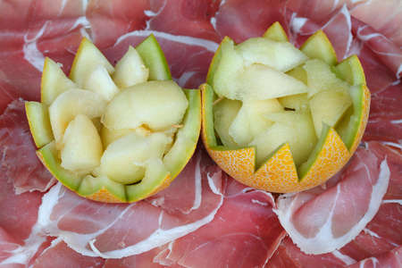 Ham and melons on a metal plate Stock Photo