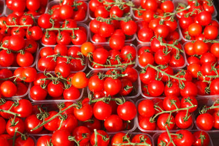 cherry tomatoes in plastic bowls on a market stall