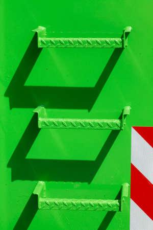 green metal steps on a green metal wall