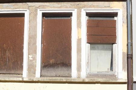 barricaded old windows on an old house