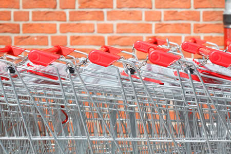 Rows of metal shopping trolleys at a supermarket