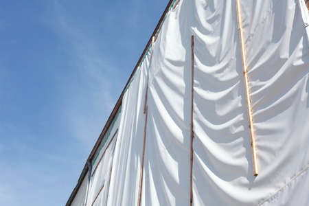 white tarpaulin on a house wall, construction site Stock Photo