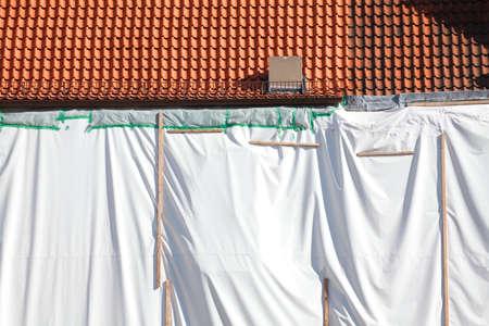 white tarpaulin on a house wall, construction site Фото со стока