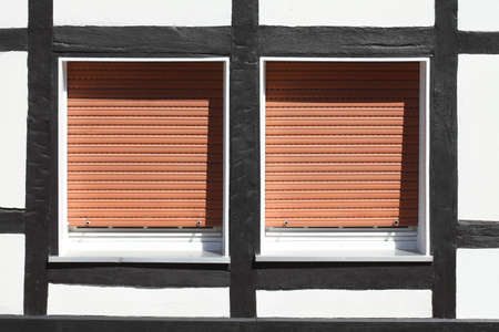White Plastic Windows on a half-timbered house with  pulled down shutters Reklamní fotografie - 91178341