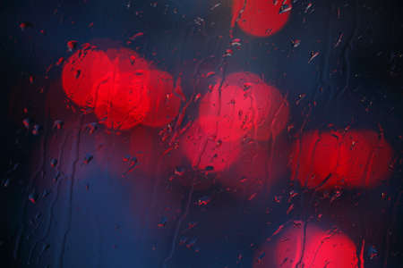 Window wet from rain, raindrops and red lights at dusk, Bremen, Germany
