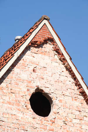 Old house roof gable with windows from brick Stock Photo