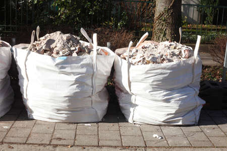 white garbage bags with rubble stones from a building site