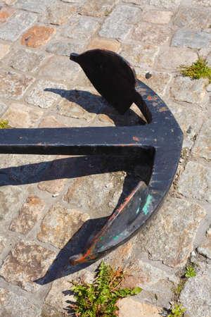 Black iron anchor, lying on the ground