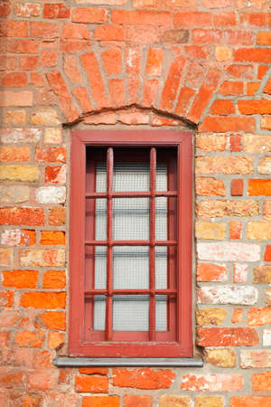 Old window with brick house wall and window bars