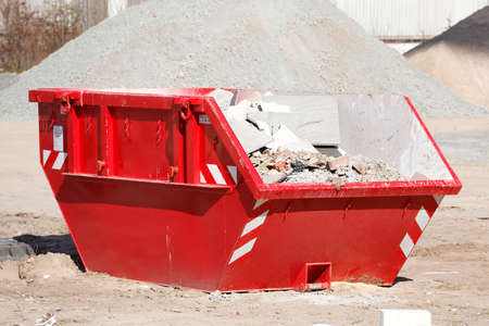 Red skip for building rubble, Germany, Europe Stock Photo
