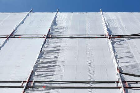 White tarpaulin, construction site, scaffolding, house facade, blue sky Фото со стока