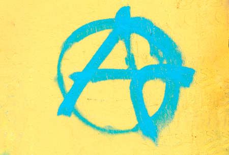 Blue A painted for anarchy on yellow wall