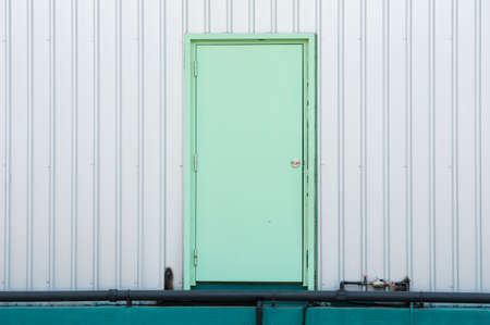 Green door on metal wall  photo