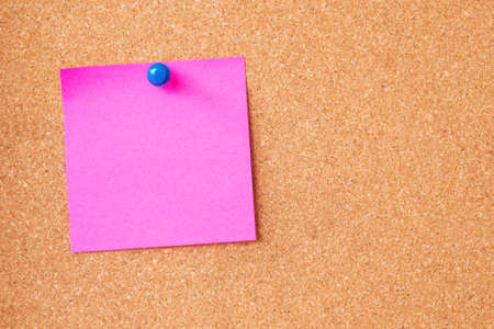 Pink sticky notes on cork board photo