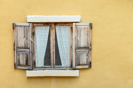 Classic window on yellow wall  photo