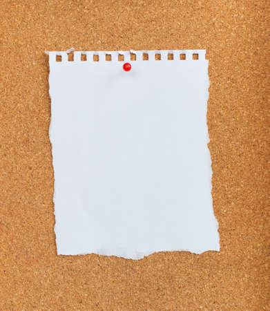 white paper with red pin on cork board  photo