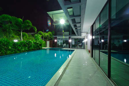 modern house exterior: Modern house with swimming pool at night