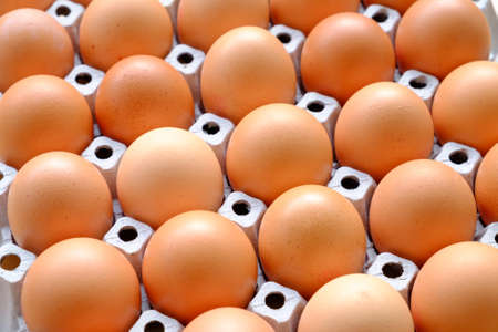 dozen: A dozen brown eggs in a carton on a wooden table Stock Photo