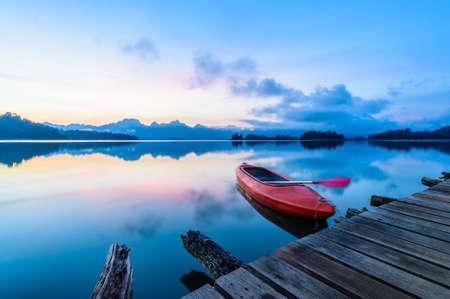 sunset lake: Canoe floating on the calm water under amazing sunrise Stock Photo