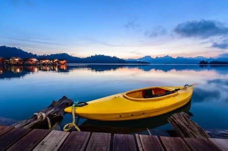 evocative: Canoe floating on the calm water under amazing sunrise Stock Photo