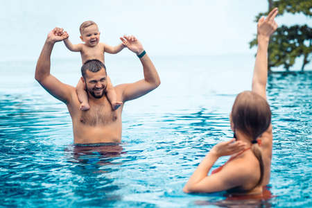 A small child and parents having fun in swimming pool on summer holiday. Phuket. Thailand. Summer vacation